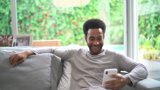 vídeos de stock, filmes e b-roll de homem novo que usa o telemóvel na sala de visitas - só um homem
