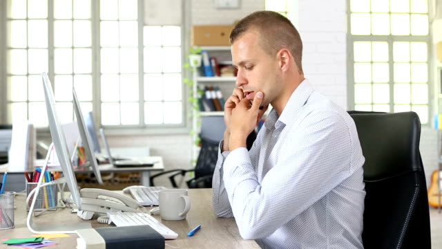 Young man using computer and talking on smart phone in modern office