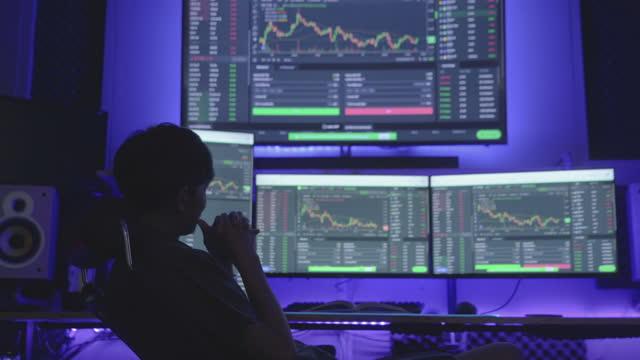 vidéos et rushes de jeune homme utilisant l'ordinateur pour apprendre et investir en bourse - marché boursier