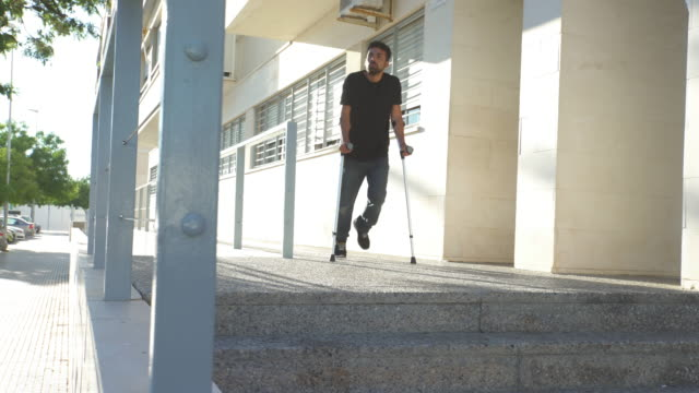 Young man using crutches while he is recovering fron an accident