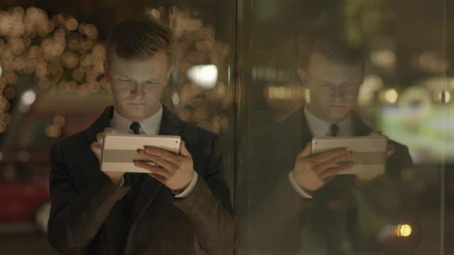 young man using digital tablet computer browsing the internet online - skjorta och slips bildbanksvideor och videomaterial från bakom kulisserna