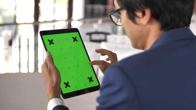 Young man using Digital tablet green screen