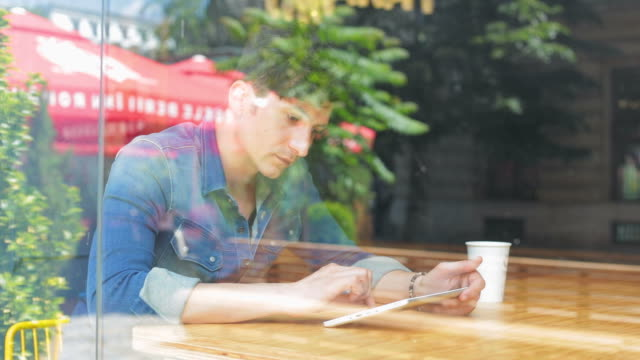 Young man using digital tablet in a coffee shop.