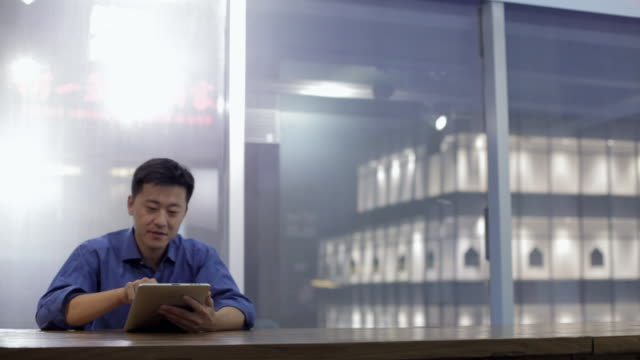 ms zi young man using digital tablet in modern office / china - using digital tablet stock videos & royalty-free footage