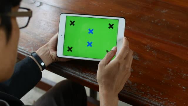 Jovem usando Tablet Digital do computador Tela verde numa mesa de madeira sobre os ombros, 4 k (UHD