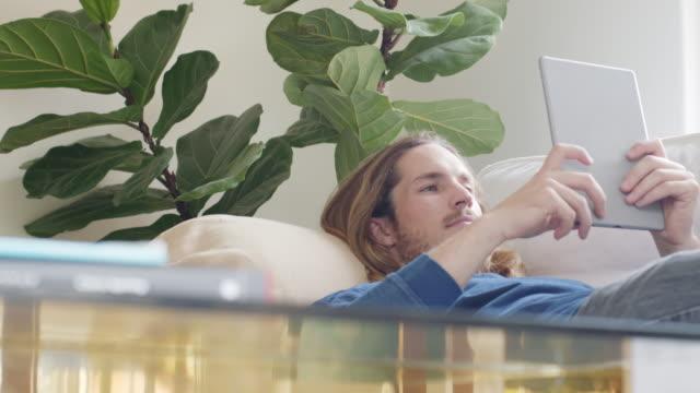 junger mann mit digital-tablette auf sofa liegend - 25 29 jahre stock-videos und b-roll-filmmaterial