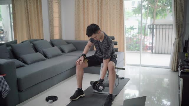 giovane che usa manubrio facendo allenamento a casa - cura della persona video stock e b–roll