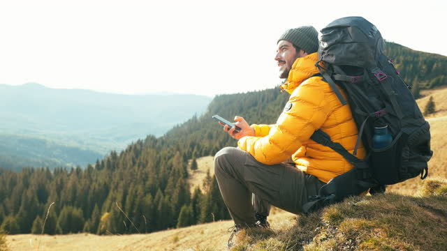 young man using his mobile phone while hiking. - choosing stock videos & royalty-free footage