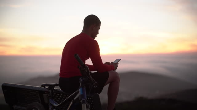 ms rv young man using his phone after mountain biking - mountain bike stock videos & royalty-free footage