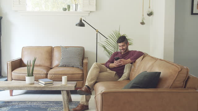young man using his phone at home - sofa stock videos & royalty-free footage