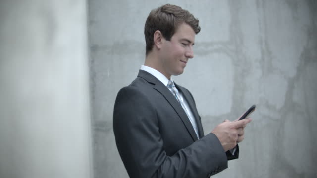 ms young man using his phone by a concrete wall - concrete wall stock videos & royalty-free footage