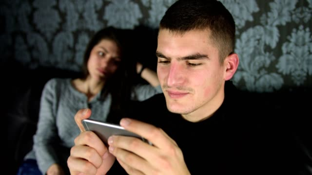 Young man using his smart phone and not paying attention to his girlfriend