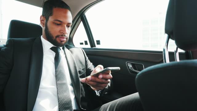 stockvideo's en b-roll-footage met jonge man met behulp van zijn smartphone onderweg. - passagiersstoel