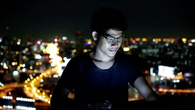 vídeos de stock, filmes e b-roll de jovem usando o laptop e olha a paisagem urbana, asiático - stationary process plate