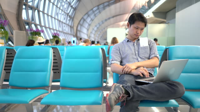 Young Man using laptop at airport, Using Laptop