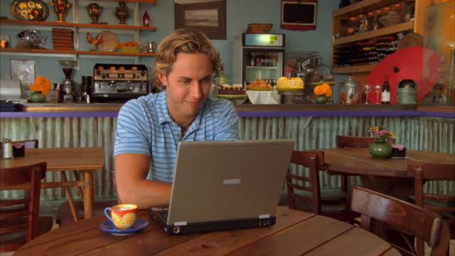 CU, Young man using laptop at coffee shop, Morro Bay, California, USA
