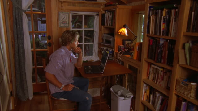ms, young man using laptop at house, cambria, california, usa - dreiviertelansicht stock-videos und b-roll-filmmaterial