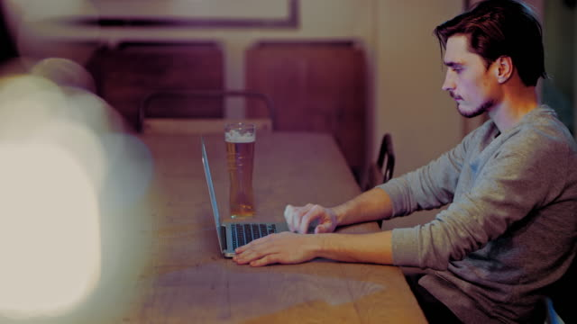 vídeos de stock e filmes b-roll de ds young man using laptop in a pub - beer alcohol