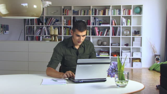 ms, pan, young man using laptop in living room - sideburn stock videos & royalty-free footage
