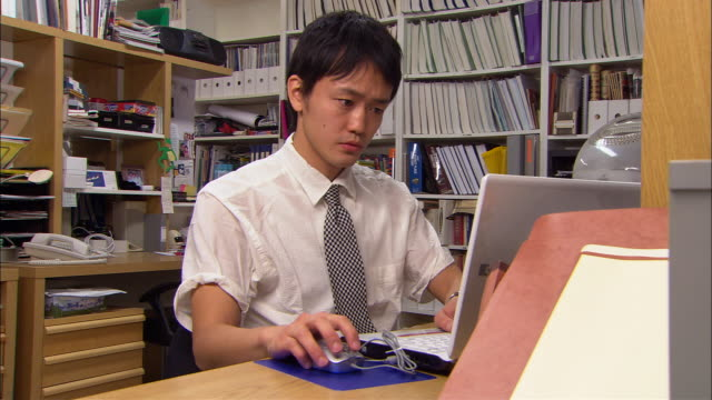 vídeos de stock, filmes e b-roll de cu, young man using laptop in office - camisa e gravata