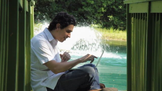 vidéos et rushes de slo mo ms young man using laptop on jetty, fountain in background / madison, florida, usa - assis en tailleur