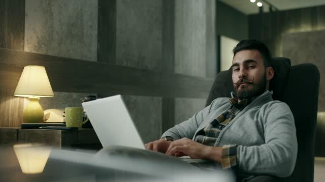 vidéos et rushes de jeune homme à l'aide d'un ordinateur portable  - masculinité