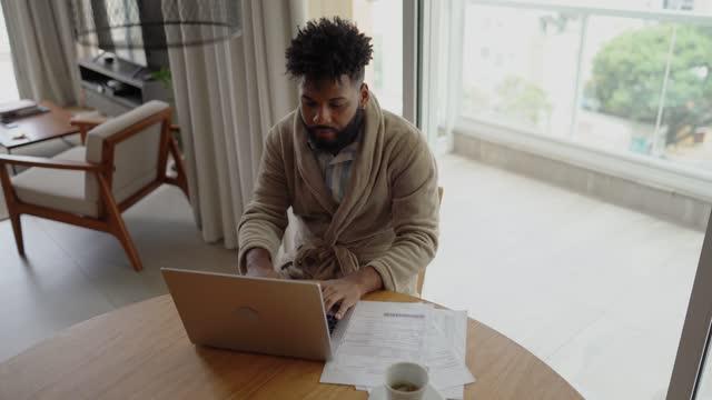 vídeos y material grabado en eventos de stock de joven que usa una computadora portátil trabajando en casa - negocios finanzas e industria