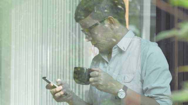 young man using mobile phone and drinking coffee - coffee drink stock videos & royalty-free footage