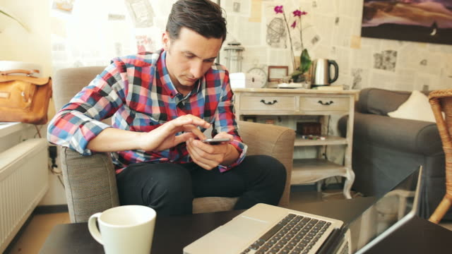 Young man using mobile phone and laptop in a coffee shop.
