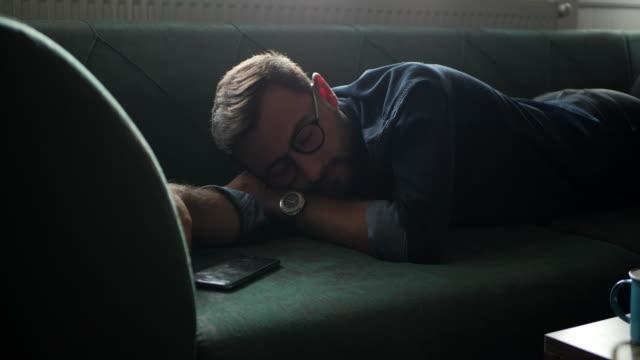 vídeos de stock e filmes b-roll de young man using mobile phone at home - confortável