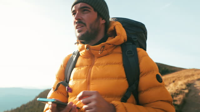 vídeos de stock e filmes b-roll de young man using mobile phone while hiking. - escolher