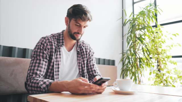 junger mann mit dem handy, während er sich im café entspannt. - tranquility stock-videos und b-roll-filmmaterial