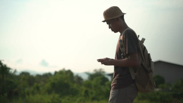 young man using mobile phone while walking - country road stock videos & royalty-free footage