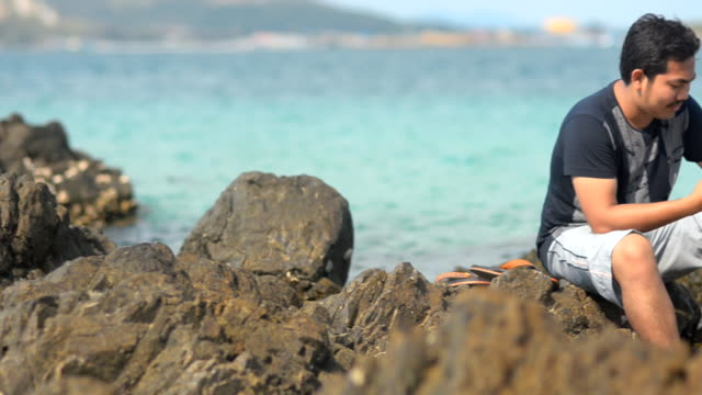 stockvideo's en b-roll-footage met young man using phone and being relaxation on the rock - men