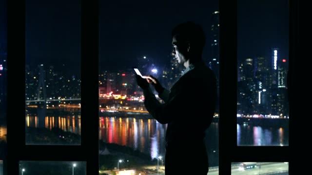 Jeune homme à l'aide de téléphone pendant la nuit par la fenêtre