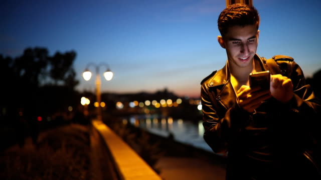young man using phone in the night - young men stock videos & royalty-free footage
