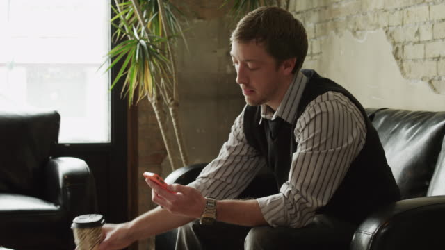 MS ZI Young man using smart phone and drinking coffee sitting on sofa / Provo,Utah,USA