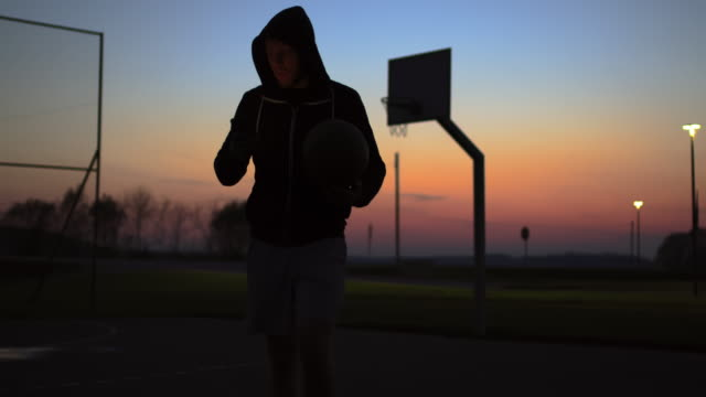 ms young man using smart phone and walking off outdoor basketball court at dusk - tracking shot stock videos & royalty-free footage