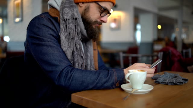 young man using smart phone in cafe - beard stock videos & royalty-free footage