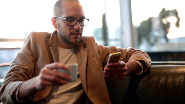 Young man using smart phone in coffee shop