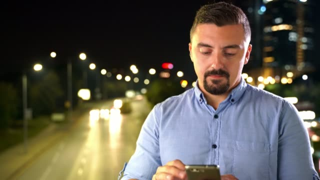 Young man using smart phone outdoors at night in front of city traffic lights