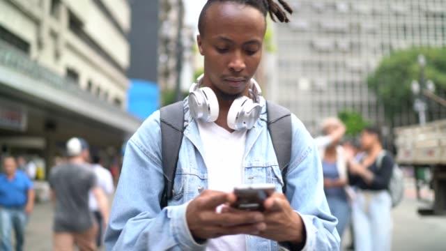 vídeos y material grabado en eventos de stock de joven usando smarthphone en la calle - 20 24 años