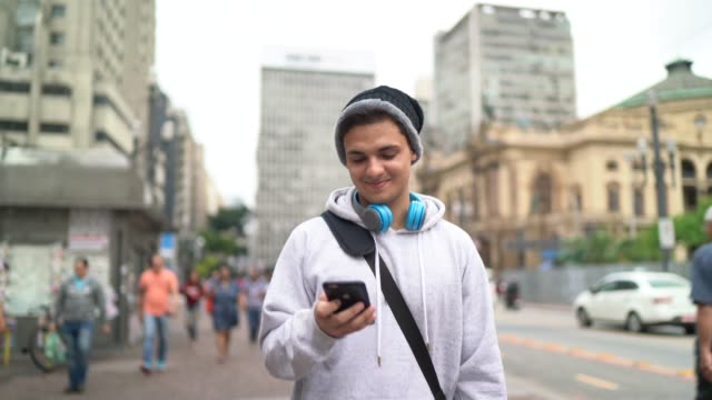 junger mann mit smarthphone auf der straße - text stock-videos und b-roll-filmmaterial