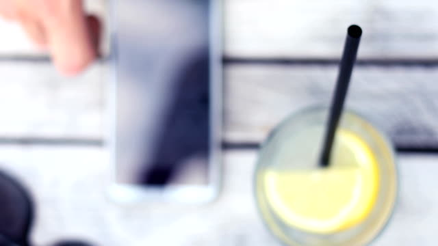 young man using smartphone and drinking lemonade - lemonade stock videos and b-roll footage