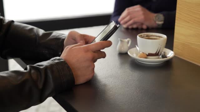 Junger Mann mit Smartphone In einem Coffee-Shop