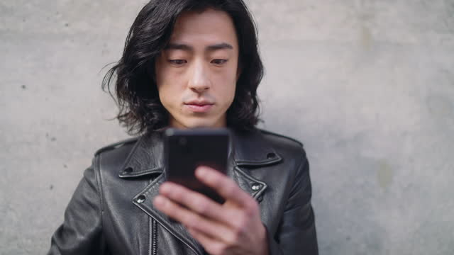 young man using smartphone while leaning against concrete wall - concrete wall stock videos & royalty-free footage