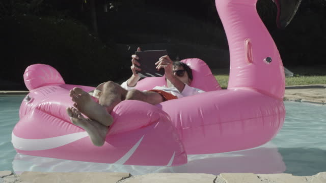 ms young man using tablet on pool float - pink shirt stock videos and b-roll footage