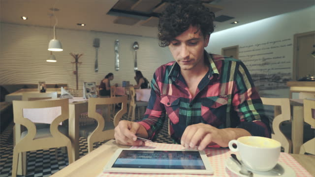 young man using tablet pc and credit card inside coffee shop. - acquisto con carta di credito video stock e b–roll