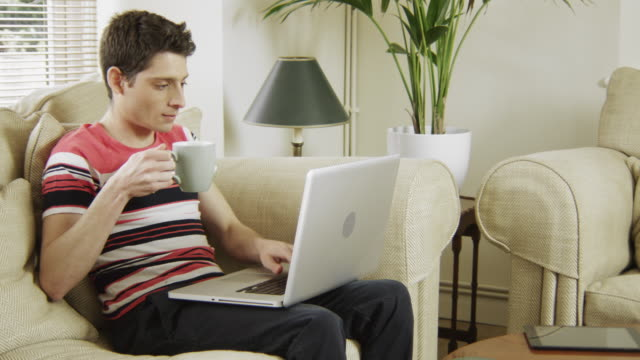 Young man using technology in his sitting room, push in, drinking coffee and typing.