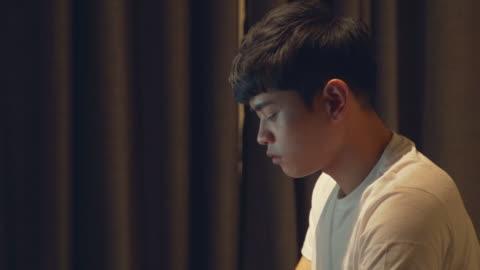 vídeos y material grabado en eventos de stock de a young man (the job seeker) using the computer in the dark room - en búsqueda